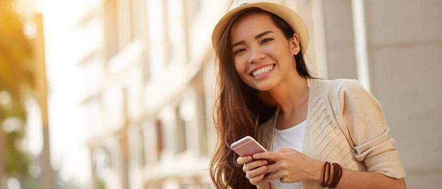 girl outdoors smiling using social media