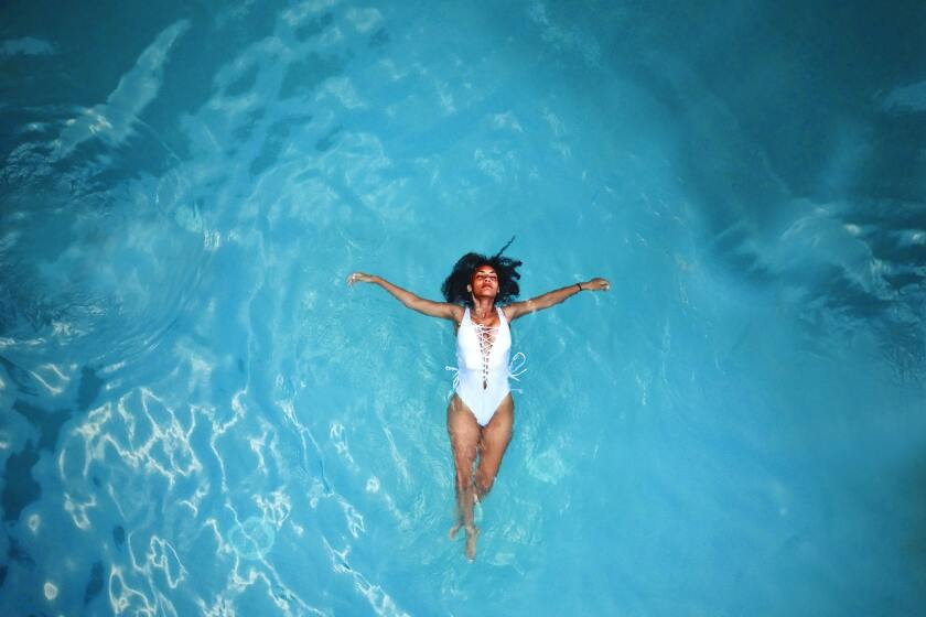 woman in white monokini swimming in body of water