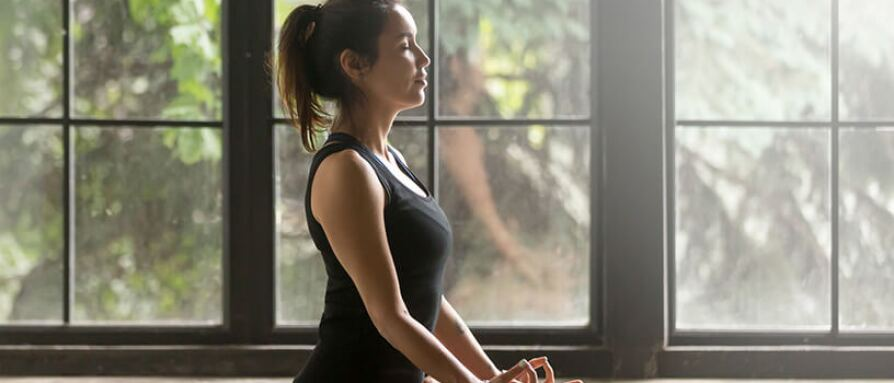 woman meditating near window