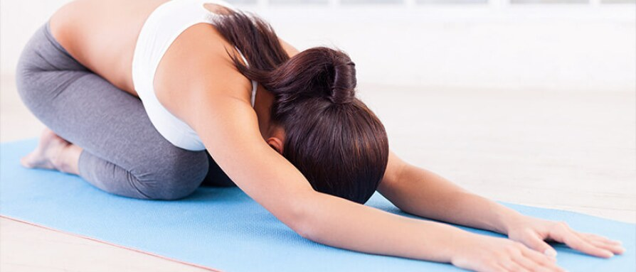 A young woman laying on a yoga mat in child's pose