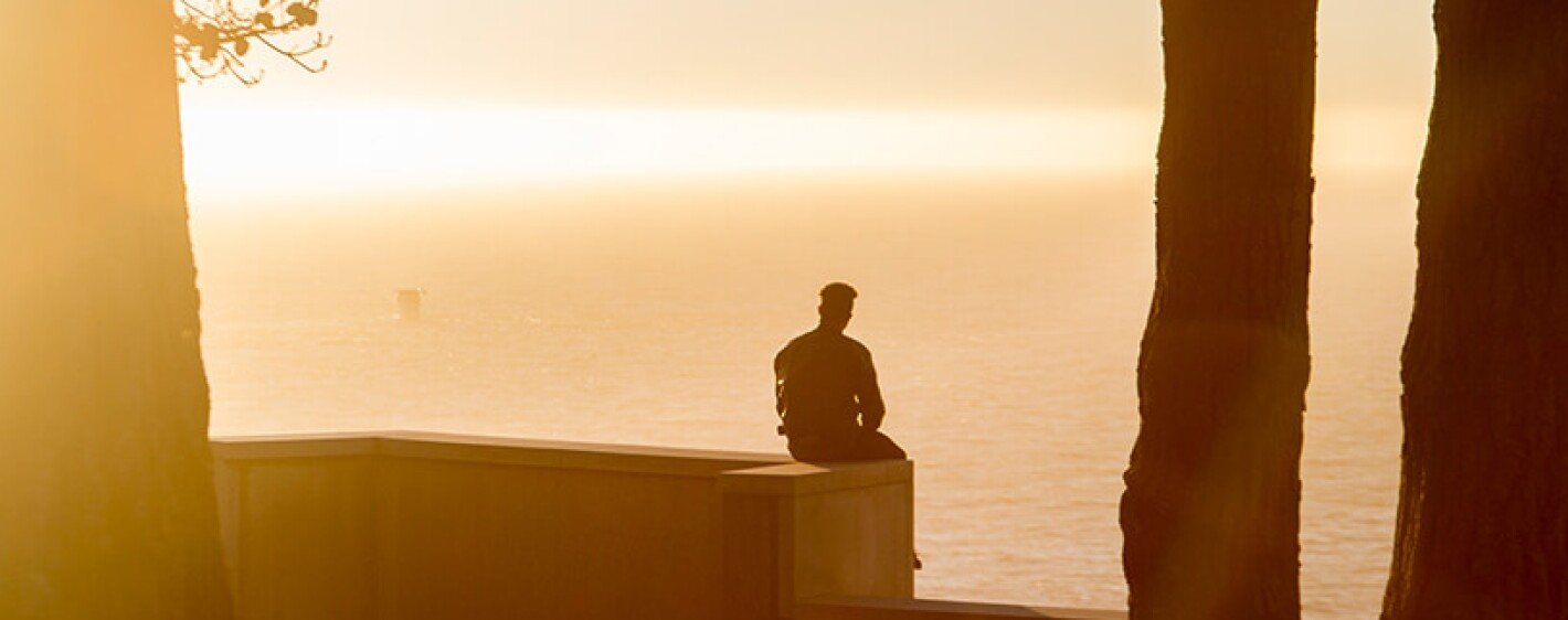 Man sitting watching a sunset