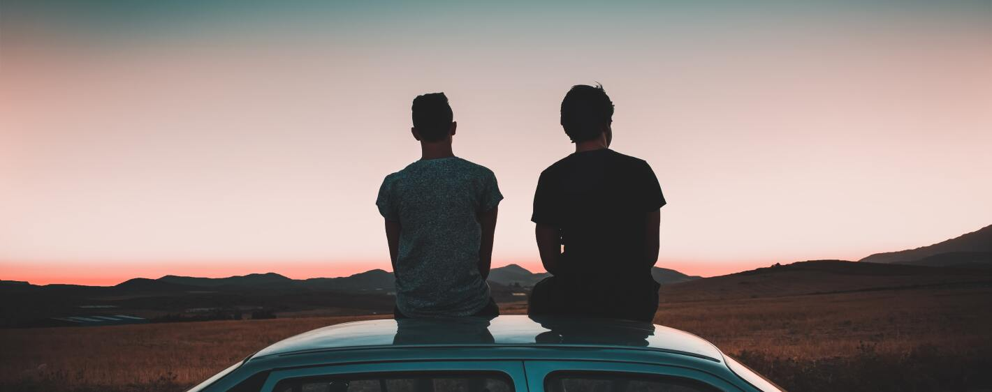 Two guys sitting on car