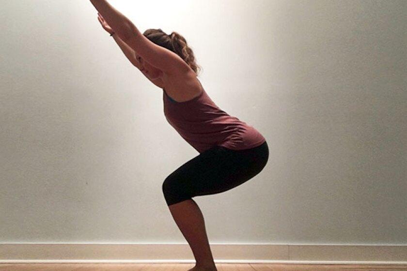 Yoga teacher in chair pose