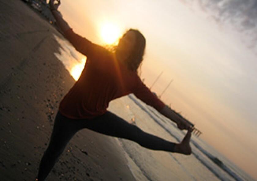 woman doing sunrise yoga at the beach