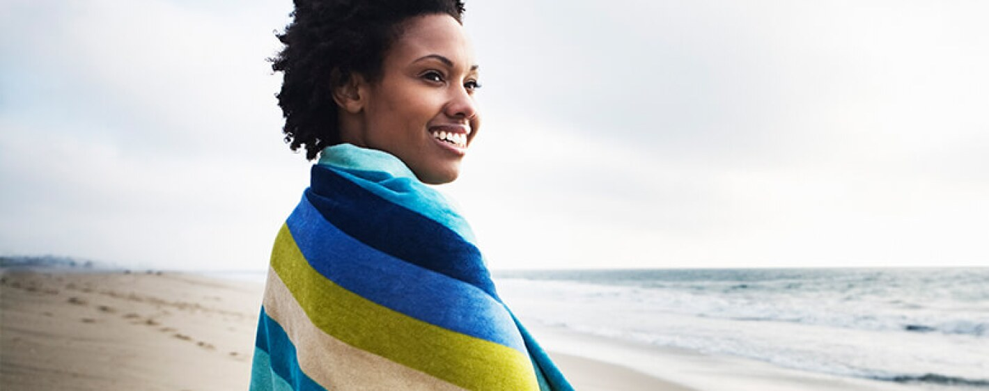 woman smiling on beach colorful towel