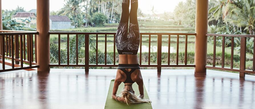A young woman in a headstand yoga pose