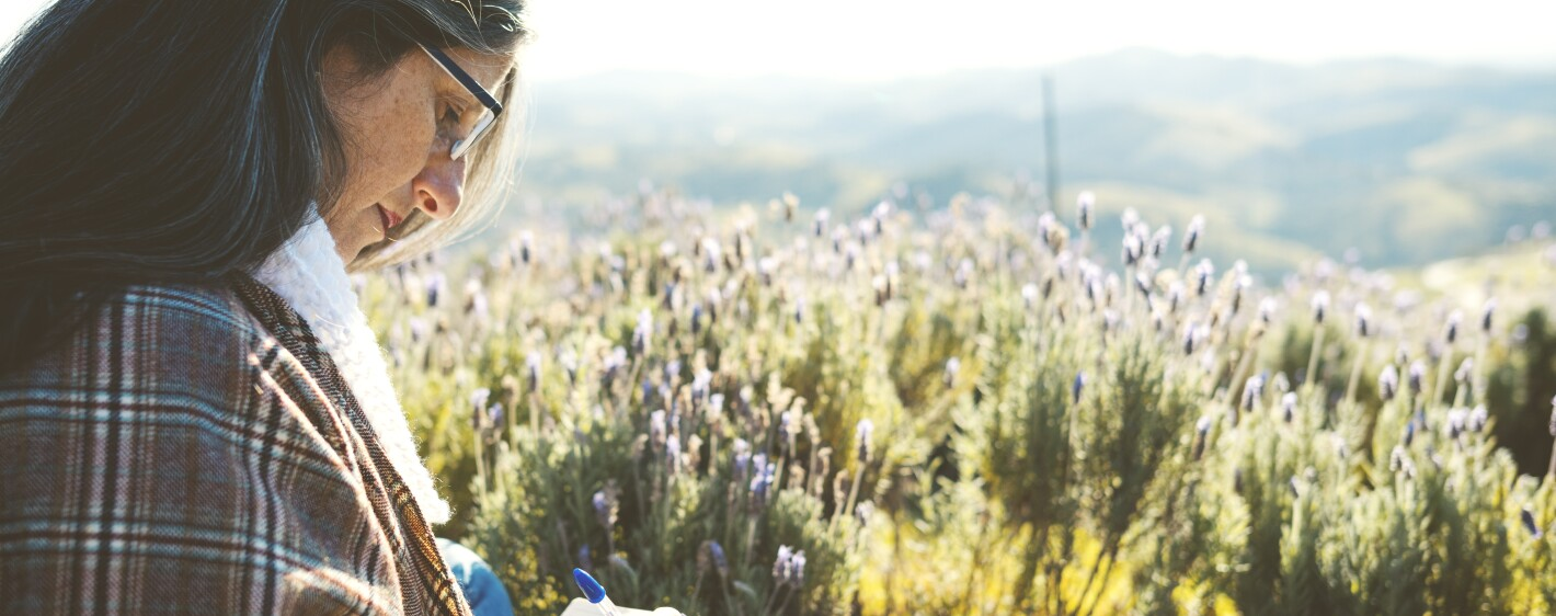 Woman sitting on the floor and writing in a lavender field, with mountains in the background.