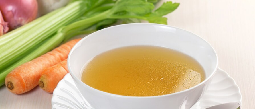 Chicken broth on a wooden table with carrots and celery