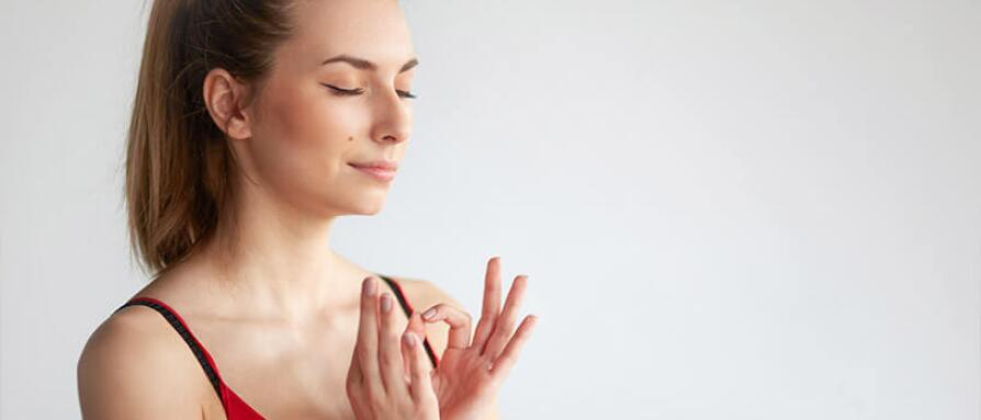 A young woman meditating with hands at heart chakra