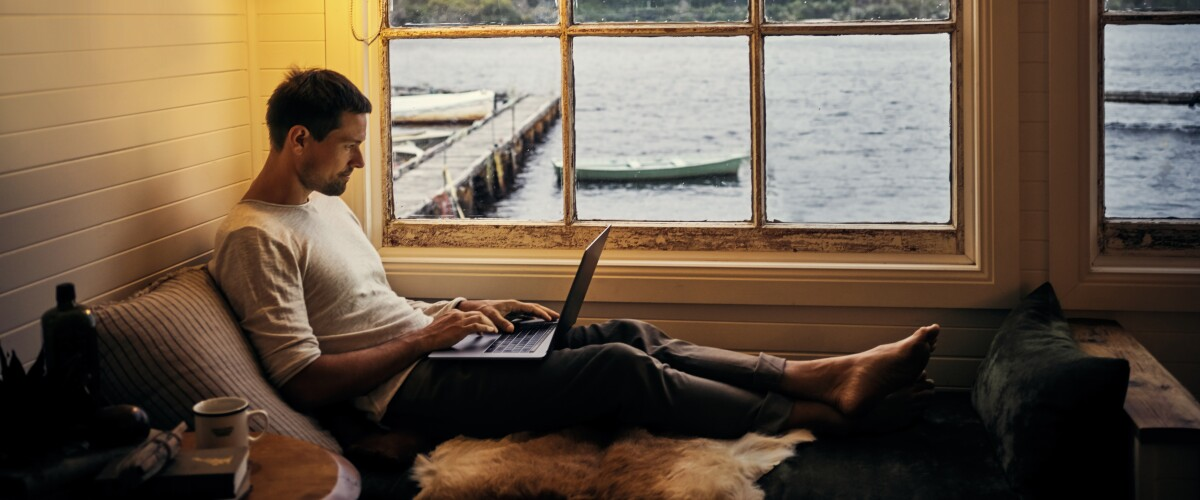 Person using a laptop while relaxing in a holiday home