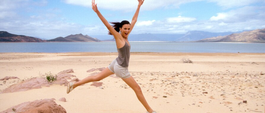 A young happy woman jumping in the air with arms out