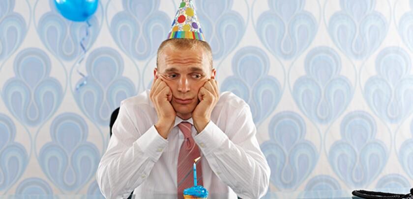 man with a birthday hat sad