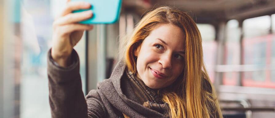 young woman taking a selfie on the bus