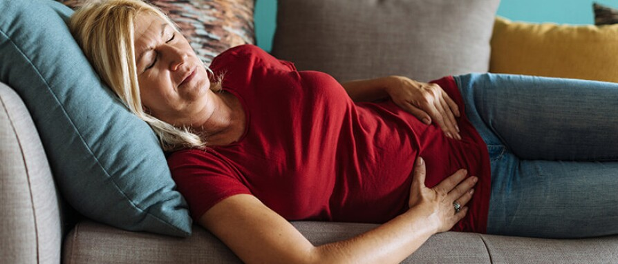 woman laying on couch with stomach pain