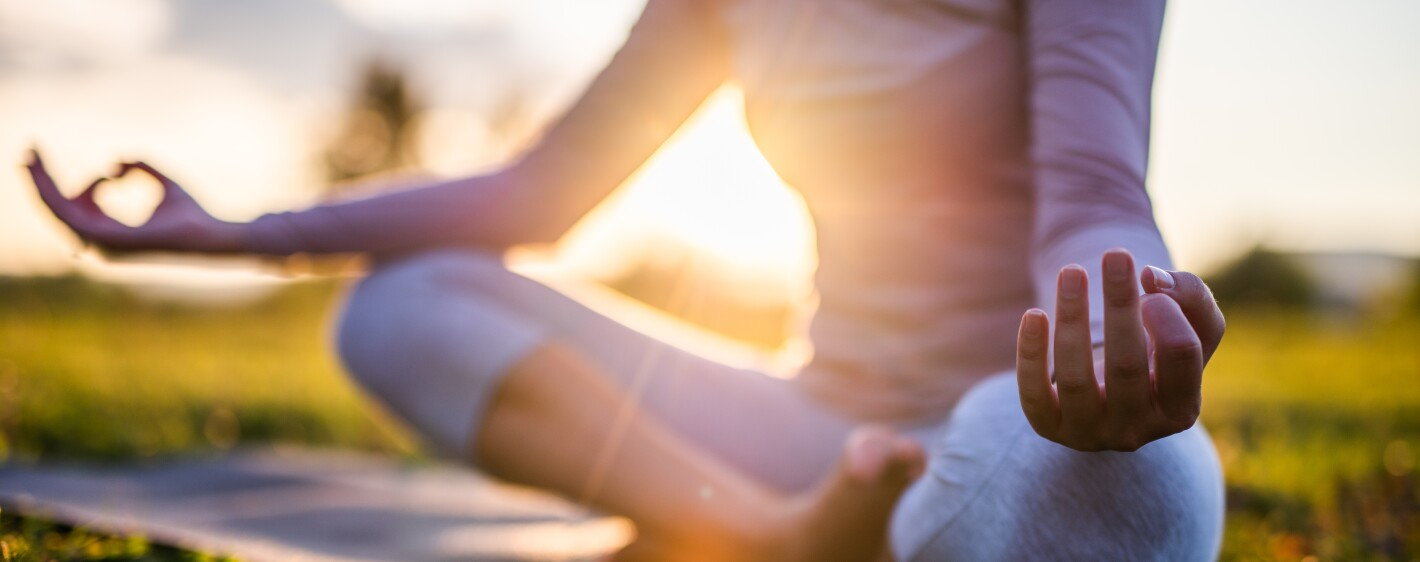 Person in seated meditation posture on yoga mat outdoors