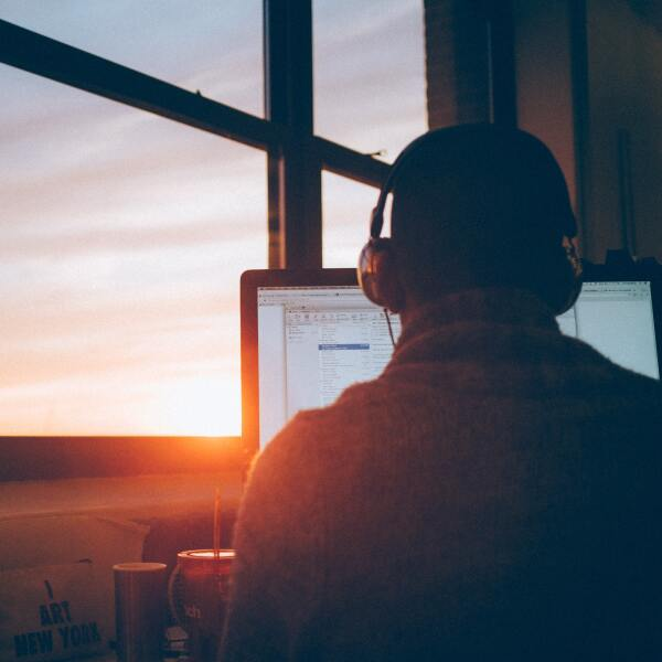 man working on desktop sunset headphones