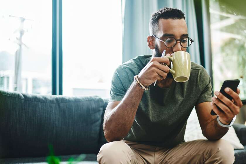 A man sipping a cup of tea and using his mobile device