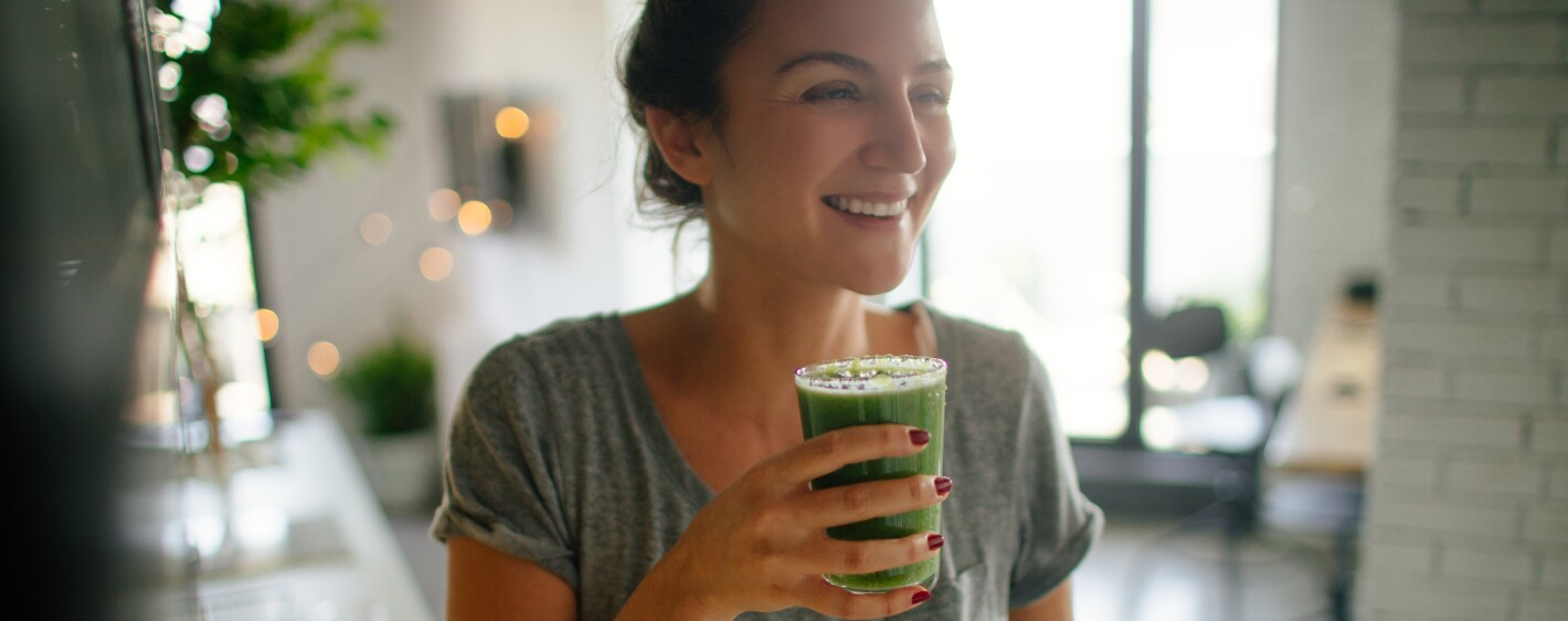 Person smiling and holding a cup of green juice