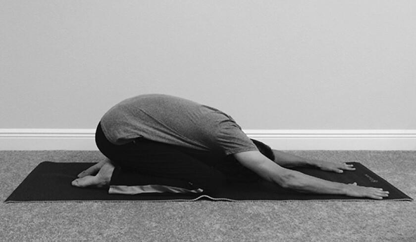 Man in child's yoga pose
