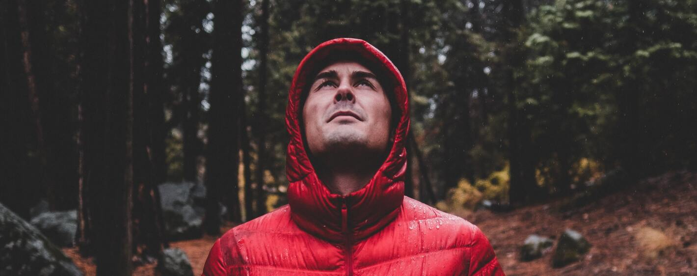 Guy in a red parka standing in the wet forest