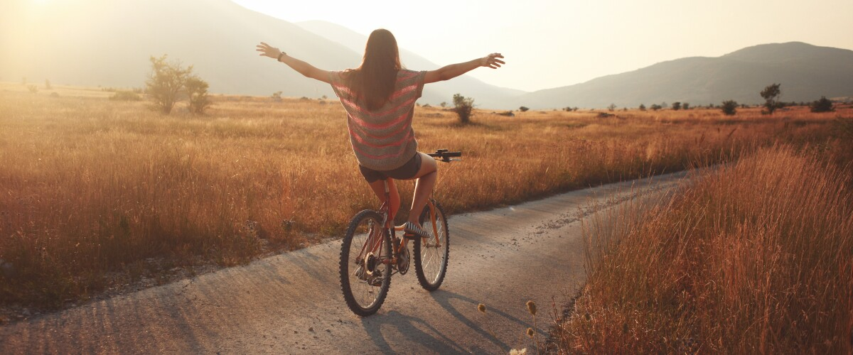 Person riding bicycle with arms up on open road