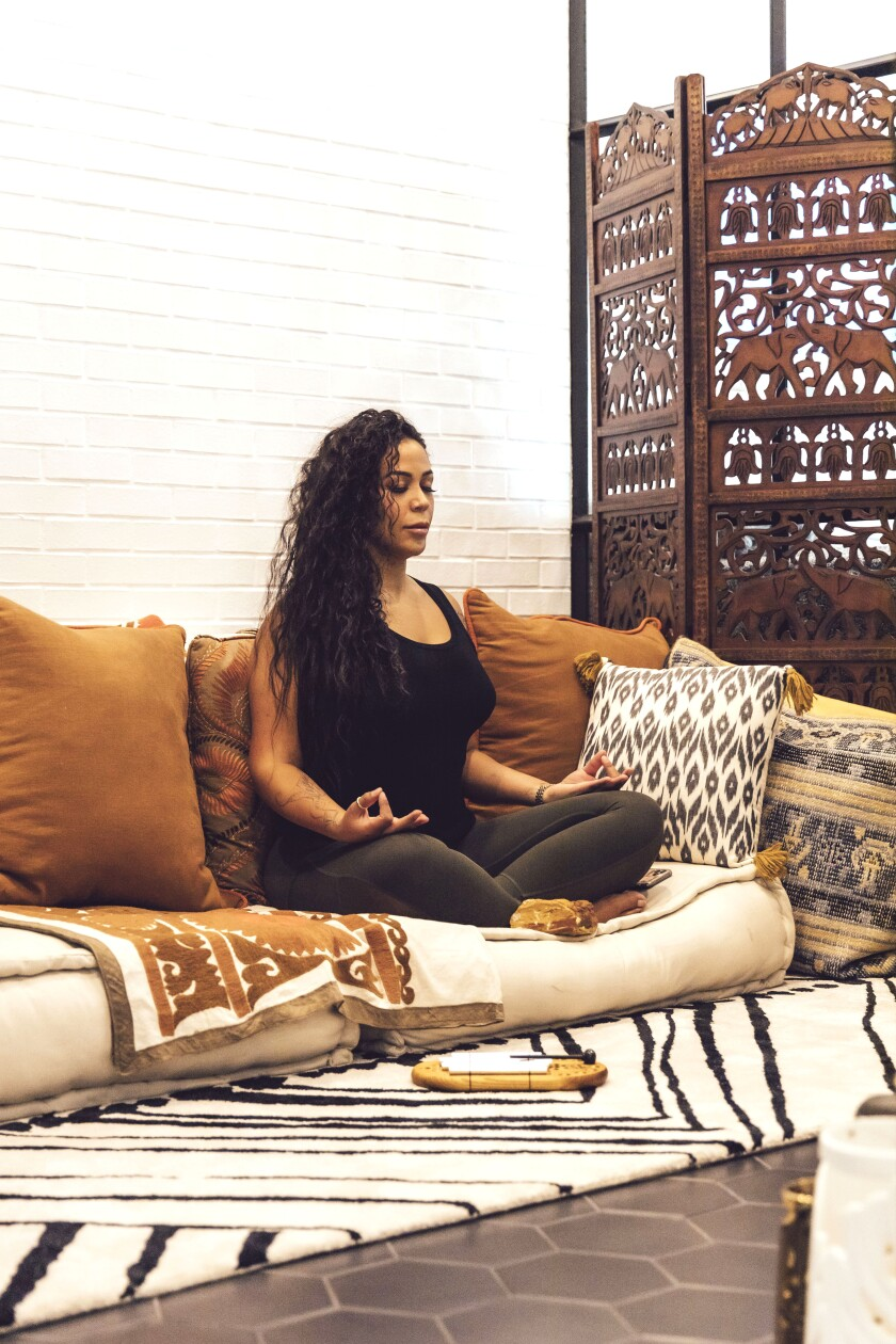 A young woman sitting on a coach meditating
