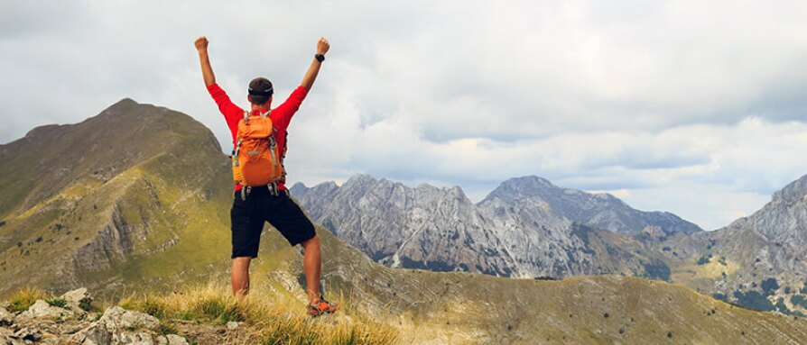 Male hiking standing on a mountain top reaching his goal