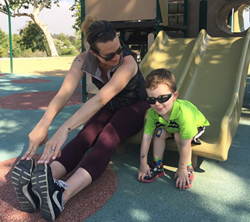 A mom and son stretching at the playground