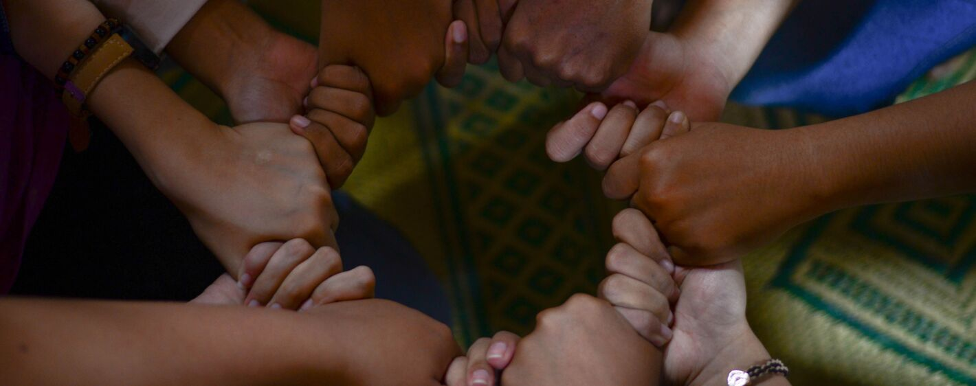 A close up of friends holding hands in a circle