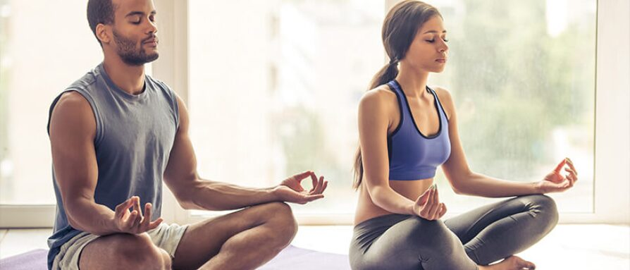 A young couple practicing meditation for stress relief