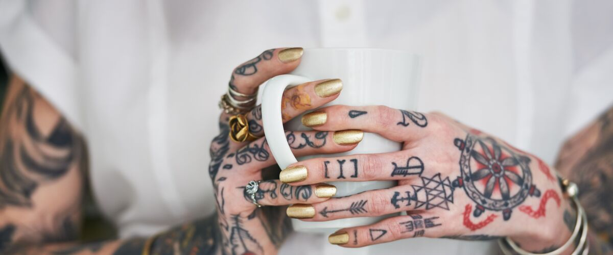 A close up of a woman holding a cup of coffee