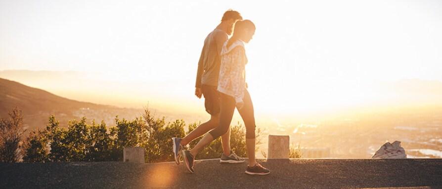 a couple walking at sunrise