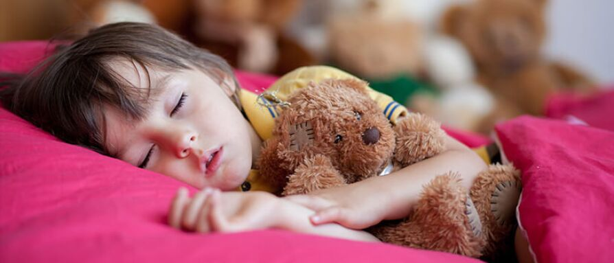 Child sleeping with a teddy bear