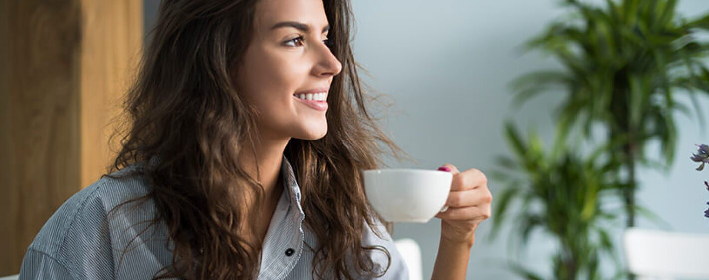 A young woman enjoying a cup of coffee in the morning
