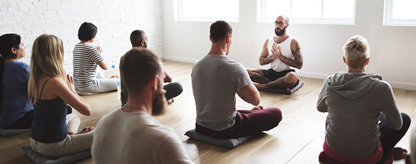 Teacher leading meditation in front of a room of students