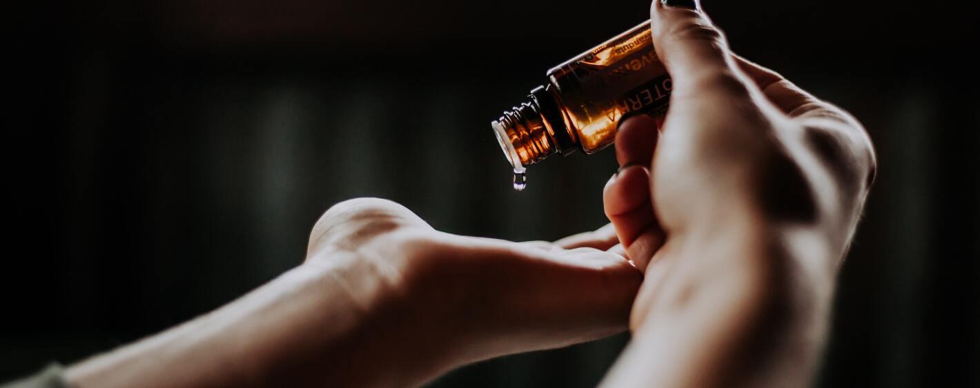 Ayurvedic oils dripping into hand