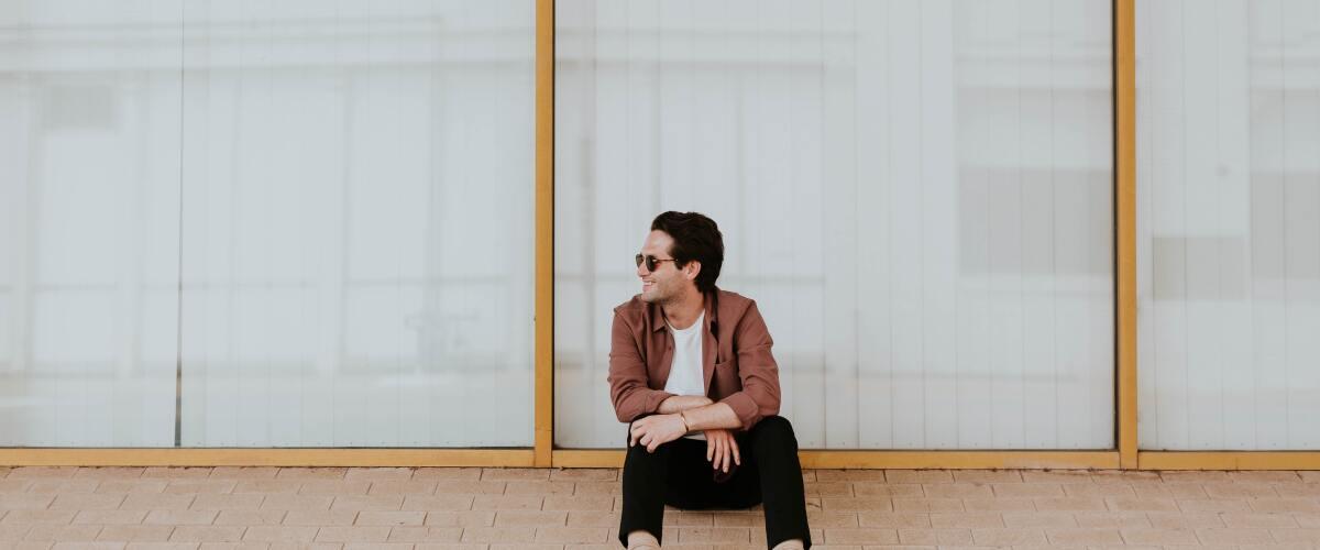A young man sitting by a sidewalk