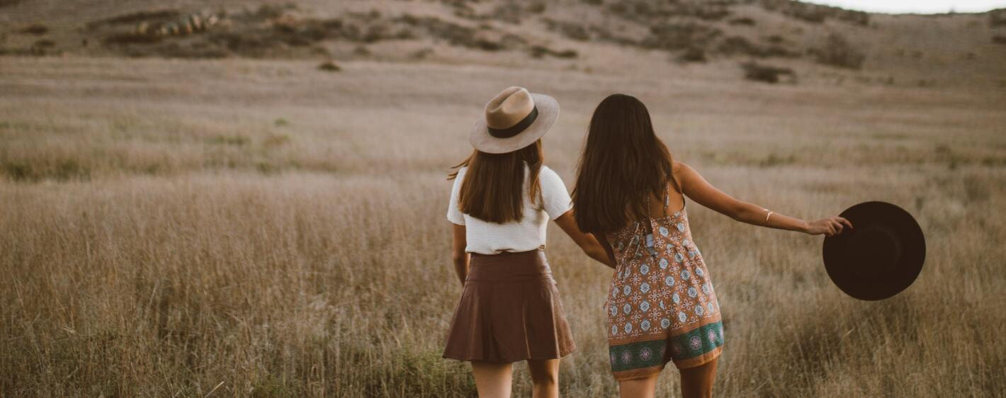 Two girls holding hands walking in a field