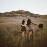 Girls holding hands walking in a field