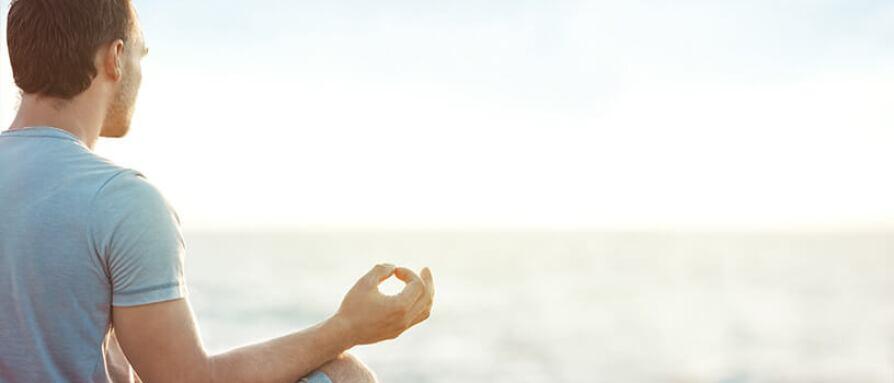 A man meditating at sunset in lotus yoga pose