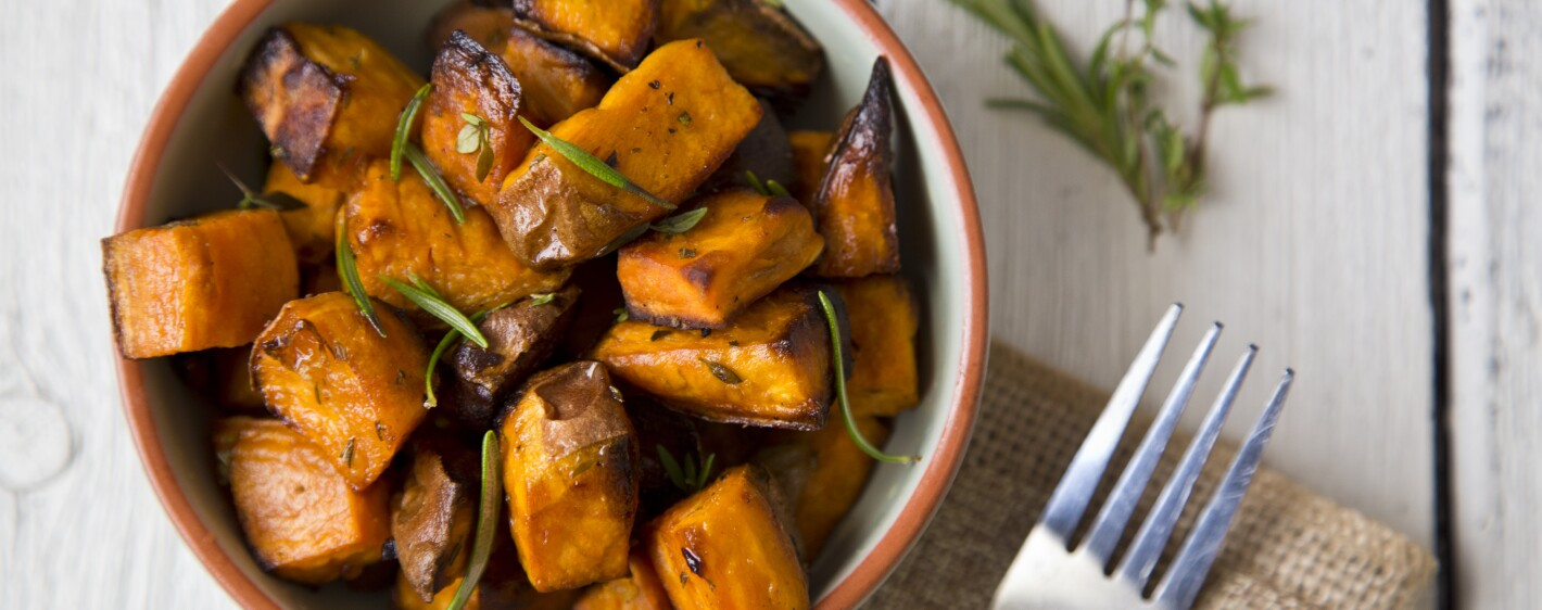 A bowl of roasted sweet potatoes with rosemary