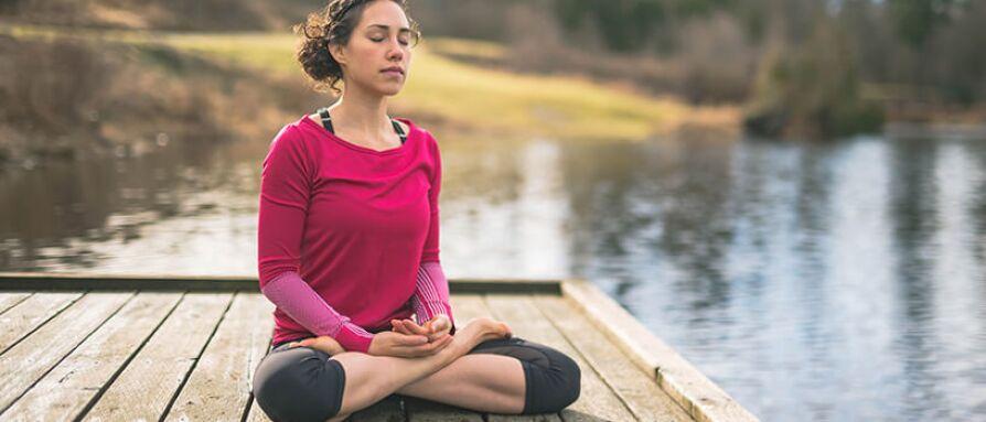 woman meditating at lake