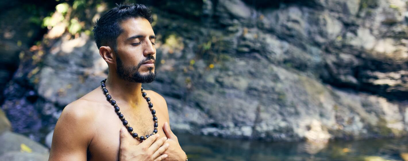 Guy meditating near a waterfall