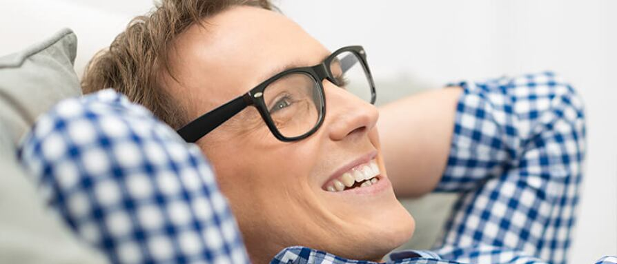 A young man laying on a couch wearing glasses and a big smile