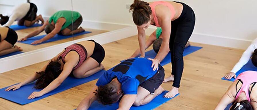 Yoga instructor adjusting a student