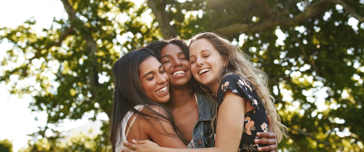 Portrait of happy three multiethnic multiracial female friends closely hugging and showing care and love for each other in park