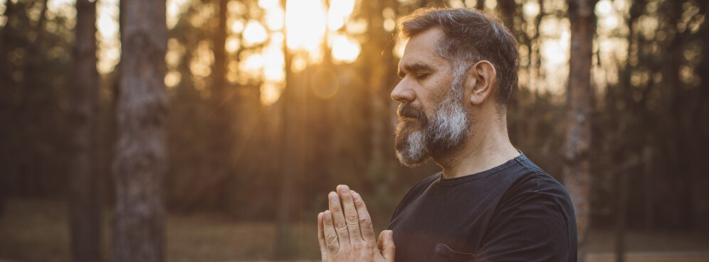 Mature man standing outside in yoga prayer position
