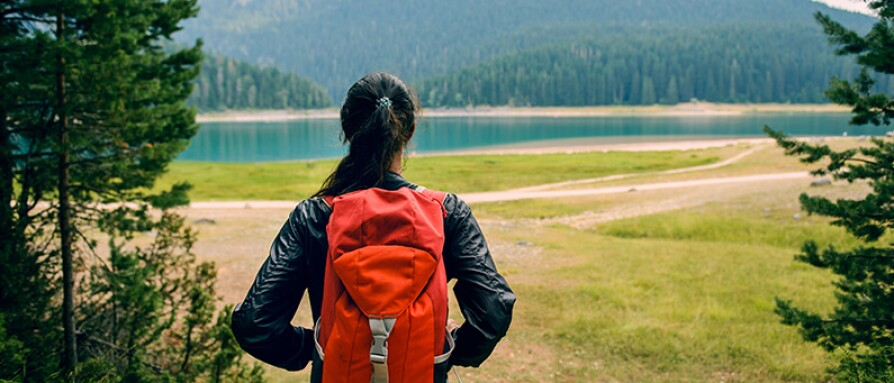 woman hiking near lake
