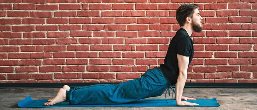 A man on yoga mat in yoga position
