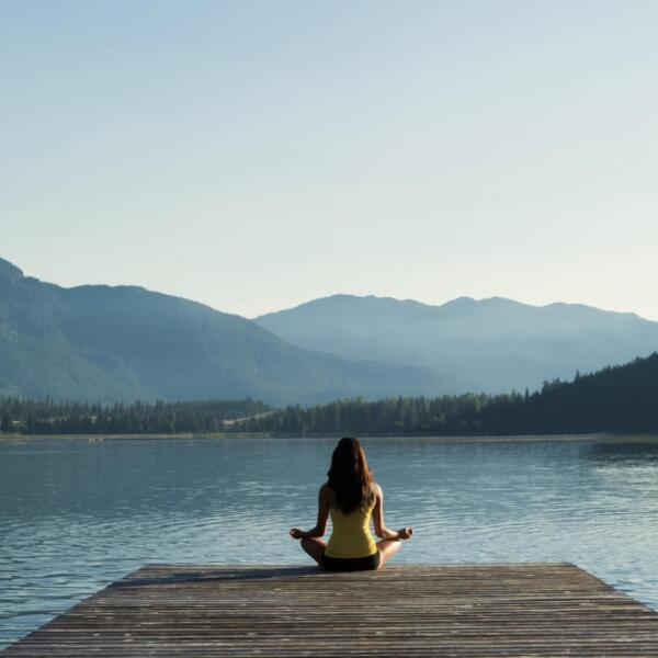 Woman meditating at a lake
